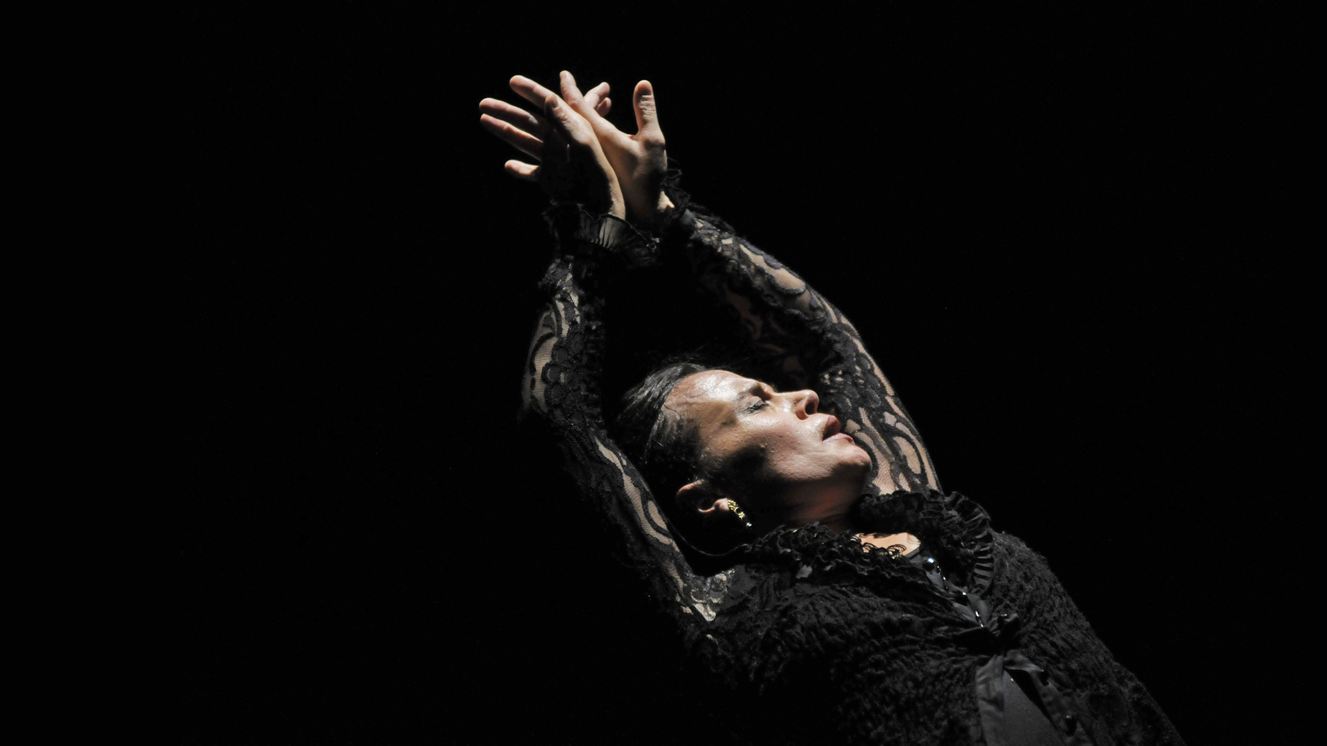 Dancer, wearing ornate black top, leans back with arms stretched over face tipped upward, eyes closed.